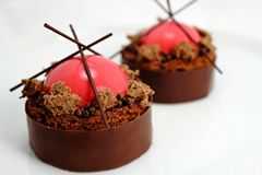 Strawberry and brownie dessert with dark chocolate jelly caviar on chocolate border royalty free stock photography