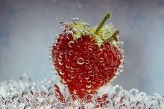 Strawberry with bubbles on blue background Stock Photos