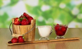 Strawberry in bucket and cup with cream Royalty Free Stock Images