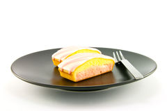 Strawberry Cake. Two pink strawberry sliced cakes with icing on the top with a small fork on a black plate with a white background Stock Images