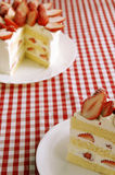 Strawberry cake. And piece of cake on a red tablecloth Royalty Free Stock Image