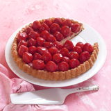 Strawberry cake. Cake with strawberries set in jelly in a pastry casing with a slice already served, white plate and pink cloth background with cake slice Stock Photo