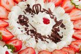Strawberry cake. Closeup of a fresh strawberry cake with sliced strawberries and chocolate Stock Image