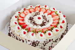 Strawberry cake in a box. Closeup of a fresh strawberry cake with sliced strawberries and chocolate in a box Stock Image