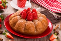 Strawberry cake. Strawberry cake with chocolate on wooden table royalty free stock images