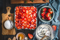 Strawberry cake , cooking preparation on rustic kitchen table with fresh berries, bowls, cutting board, sugar and cream Royalty Free Stock Photos