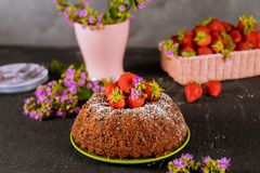 Strawberry cake and flowers, basket with fresh strawberries. Strawberry bundt cake and flowers, basket with fresh strawberries, homemade, pound, fruit, food stock images