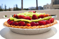 Strawberry cake. Fruit cake dessert with kiwis and strawberries set on a table outside ready to be eaten Stock Images