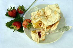 Strawberry cake. Homemade strawberry cake on a white saucer, meringue pie, cake, double meringue with strawberries, with silver forks; summer cake royalty free stock photo