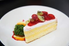 Strawberry cake and kiwi. On a plate stock photography