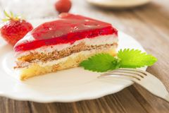 Strawberry cake with leaf of mint on plate on wooden table background Royalty Free Stock Images