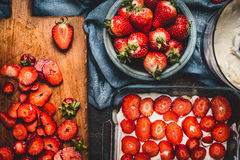 Strawberry cake making with sliced berries and cream on dark rustic background Stock Photography
