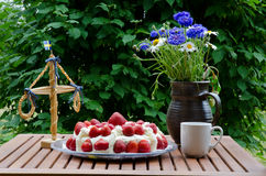 Strawberry cake at midsummer. On a table with a small midsummer tree and a vase summer flowers Royalty Free Stock Photography
