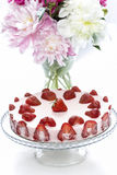Strawberry cake and pink peonies in the vase Royalty Free Stock Photo