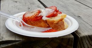 Strawberry and Cake. A plate of cake, strawberries and cream, sits ready to eat, on a rustic picnic bench Stock Photo