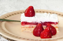 Strawberry cake on the plate and strawberries on the table Stock Photos