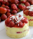 Strawberry cake. Small strawberry cake with pudding and white chocolate, with strawberries in the background royalty free stock photo