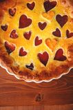 Strawberry cake for Valentine`s Day with hearts on a wooden back Royalty Free Stock Images