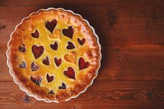 Strawberry cake for Valentine`s Day with hearts on a wooden back Stock Photography