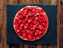 Strawberry Cake. With vanilla cream on a black slate and a wooden table Stock Photo