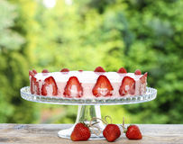 Strawberry cake on wooden table in lush summer garden Royalty Free Stock Photography