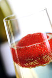 Strawberry in Champagne. Closeup of strawberry in champagne, with bottle behind. Shallow DOF stock image