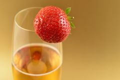 Strawberry with champagne stock images. Glass of champagne with strawberry stock images. Champagne on a golden background with copy space for text. Festive stock photography