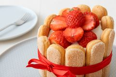 Strawberry Charlotte, French strawberry dessert. Charlotte, French dessert with strawberries, tied up with a scarlet ribbon, coffee cup, bowl with strawberries royalty free stock images