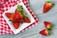 Strawberry and checkered napkin on wooden background, top view Royalty Free Stock Image