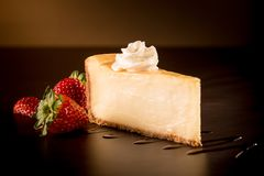Strawberry Cheescake in a dark ambient. Strawberry Cheescake with cream in a dark ambient royalty free stock photography