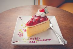 Strawberry cheese cake dessert put on white plate that decorate with jam. Selective focus royalty free stock photos