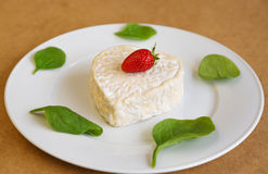 Strawberry cheese in the shape of a heart on a white plate Royalty Free Stock Image