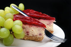 Strawberry cheesecake. With fresh grapes on a black background royalty free stock photography
