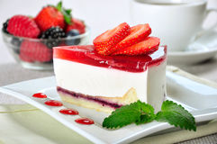 Strawberry cheesecake. Piece of strawberry cheesecake on white plate with coffee cup Stock Photos