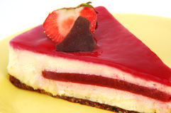 Strawberry cheesecake. On a yellow plate isolated on white Royalty Free Stock Photos