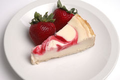 Strawberry Cheesecake. A slice of strawberry cheesecake and two strawberries royalty free stock photos