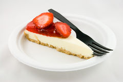Strawberry Cheesecake with Fork. Slice of strawberry chessecake with a black fork on a white plate with a white background Royalty Free Stock Images