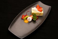Strawberry cheesecake served with fruit Stock Image