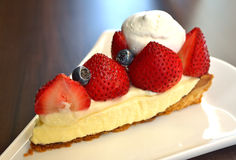 Strawberry cheesecake. Slice with fresh berries and cream on top Stock Photos