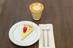 Strawberry cheesecake on the wooden table. A piece of strawberry cheesecake on the wooden table royalty free stock photography