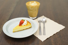Strawberry cheesecake on the wooden table. A piece of strawberry cheesecake on the wooden table stock photos