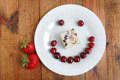 Strawberry cherry with cake in shape of smile Royalty Free Stock Photo