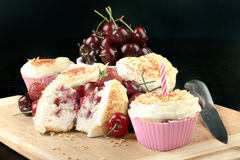 Strawberry Cherry Muffin With A Candle, Horizontal. Close-up of a cream cheese iced strawberry cherry muffin with a pink candle surrounded by fruit and other Royalty Free Stock Photo