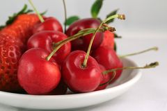 Strawberry and cherry on a plate Stock Images