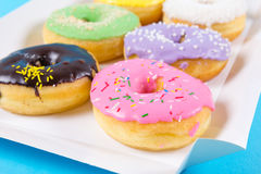 Strawberry, chocklate and other donuts in paper box on blue background Royalty Free Stock Image