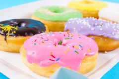 Strawberry, chocklate and other donuts in paper box on blue background Royalty Free Stock Photos