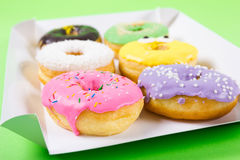 Strawberry, chocklate and other donuts in paper box on blue background Stock Photo