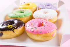 Strawberry, chocklate and other donuts in paper box on pink background Stock Images