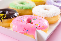 Strawberry, chocklate and other donuts in paper box on pink background Royalty Free Stock Image