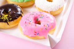 Strawberry, chocklate and other donuts in paper box on pink background Royalty Free Stock Photo